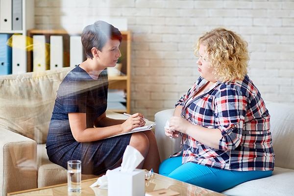 Mielenterveyden ammattilainen juttelee päihderiippuvaisen potilaan kanssa.