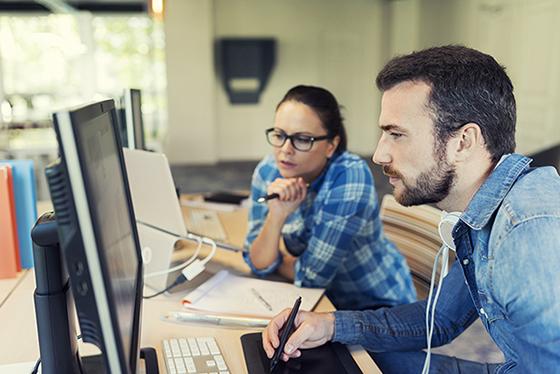 Työpaikkaohjaaja ohjaa opiskelijaa tietokoneella.
