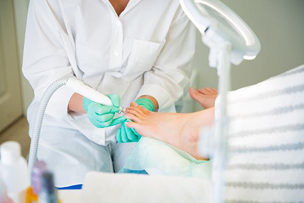 Jalkojenhoitaja tekemässä kynsihoitoa varpaisiin.