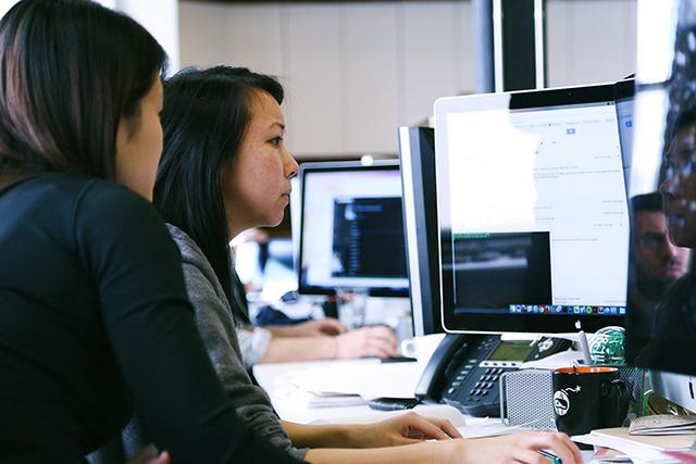 Kaksi naista tietokonenäyttöjen edessä työskentelemässä.
