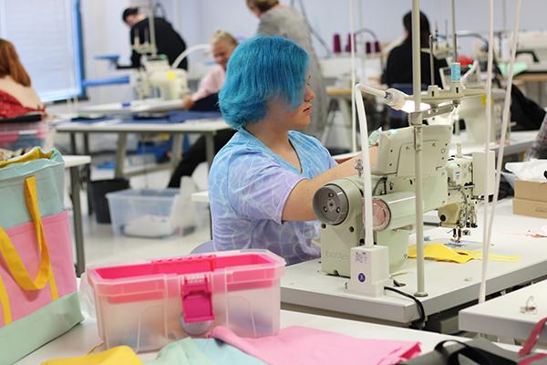 Tekstiiliopetuksen työsali, ompelukone ja opiskelija, tarvikkeita.