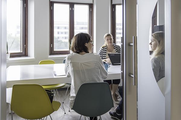 Kolme henkilöä pöydän äärellä. Kaksi vasemmanpuoleista henkilöä katsovat oikealla olevaa. Pöydällä on kannettava tietokone, kahvikuppi ja paperi.