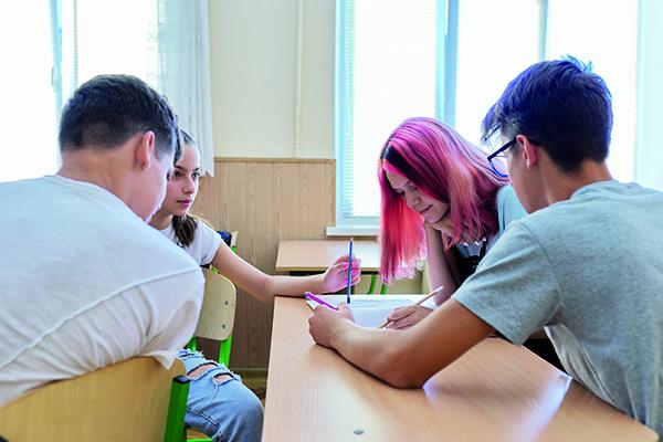 Neljä nuorta henkilöä pöydän ääressä.