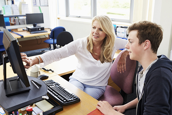 Kaksi henkilöä tietokoneen äärellä.